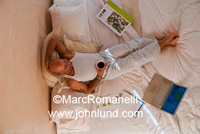 Photo of a man laying on a bed with a cup of coffee and his laptop computer. He is a laid back dude working from home. He has papers spread around, is barefoot, dressed all in white, and has a tattoo on his arm.